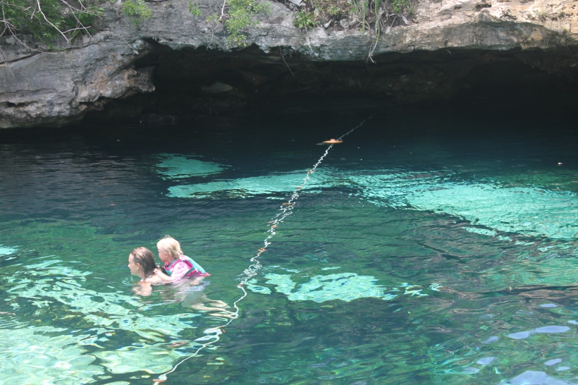 Mommy carries Lily on her back as she swims through Cenote Azul