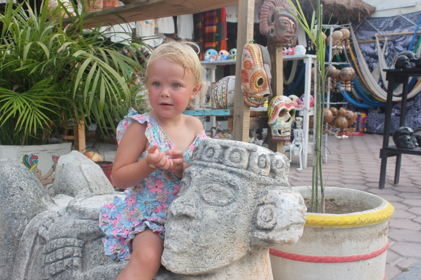 Lily rides on a Mayan carving / Tulum